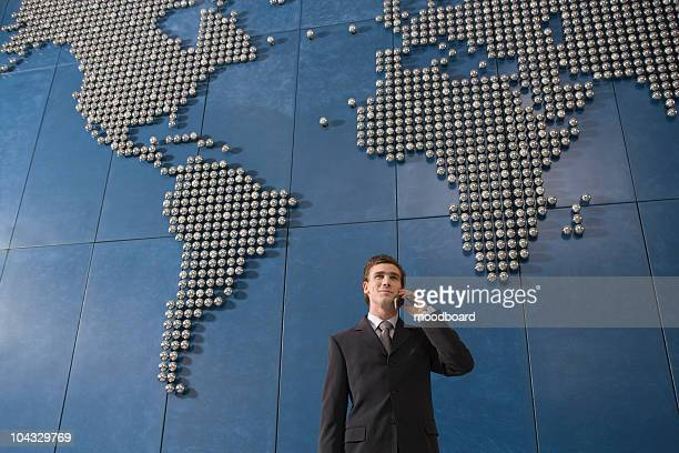 Business man using mobile phone in front of world map in office