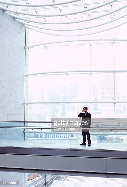 Business man using mobile phone in office concourse