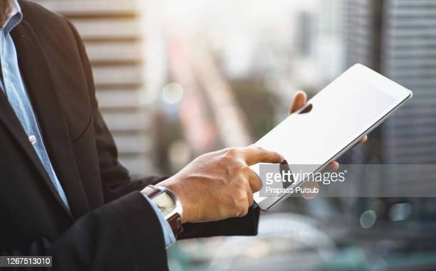 business man using mobile smart phone, busy working on laptop computer browsing internet or checking internet application on smartphone with digital tablet and business data on office desk, close up - contract stock pictures, royalty-free photos & images