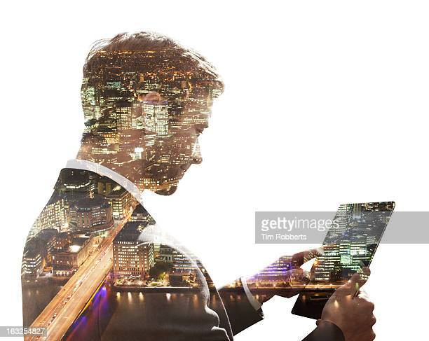 Business man using tablet, with city view at night