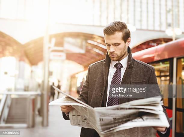 Business Mann wartet mit dem Zug am Bahnhof