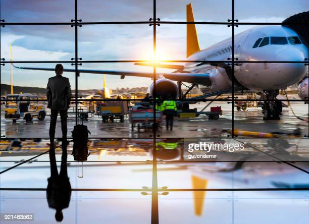 business man waiting to board a flight in airport - aircraft stock photos and pictures