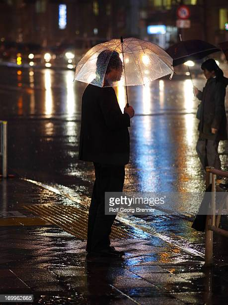 CONTENT] A business man waiting with his umbrella at a stoplight at night during heavy rain in Tokyo