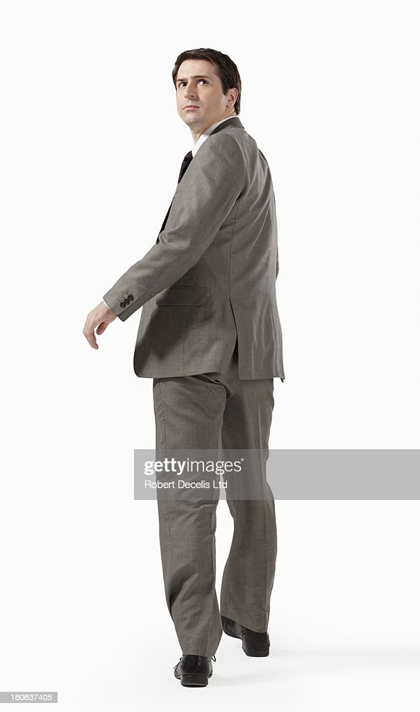 business man walking away from camera looking back stock photo