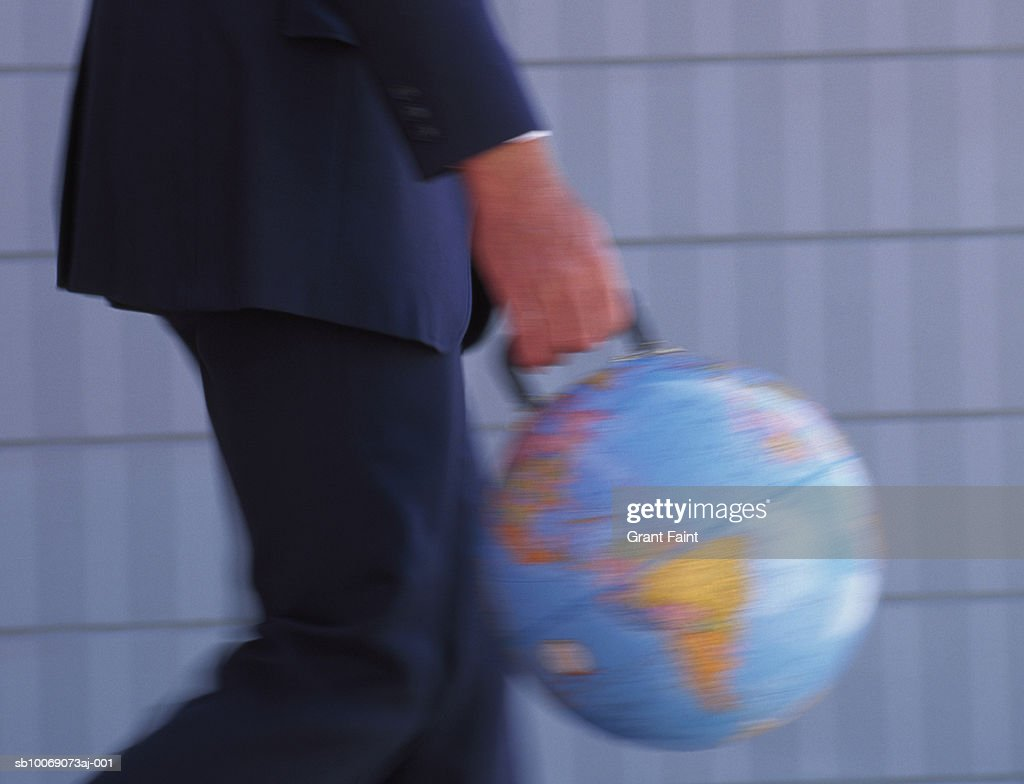Business man walking, carrying globe with handle, mid section : Stockfoto