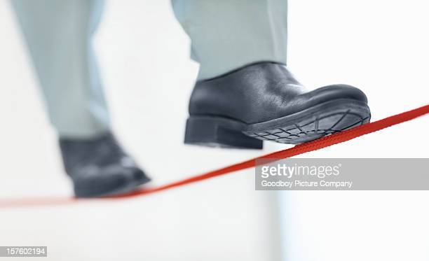 Business man walking on thin line depicting uncertainty job