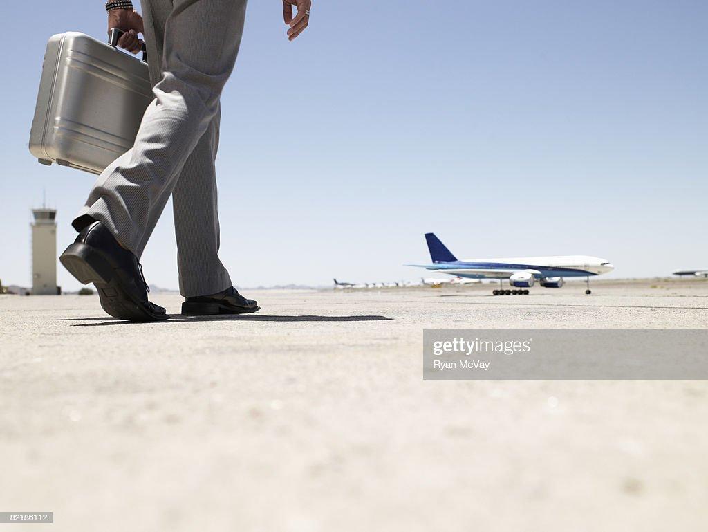 business man walking toward airplane : Stock Photo