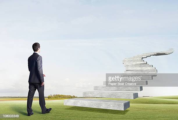Business man walking toward floating stairs
