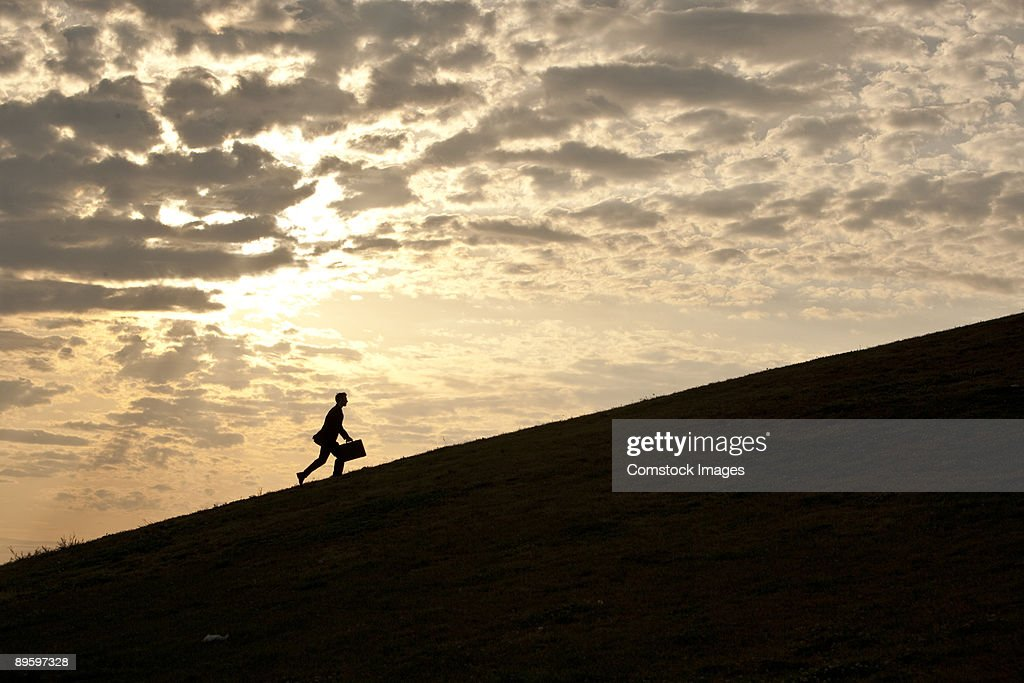 business man walking up hill : Stock Photo