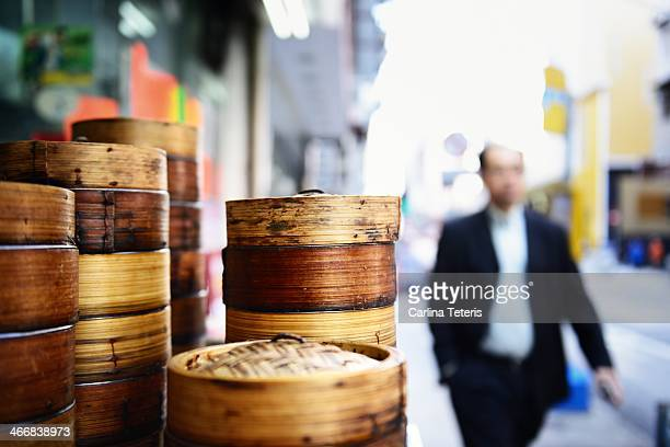 Business man walks by a stack of dim sum baskets