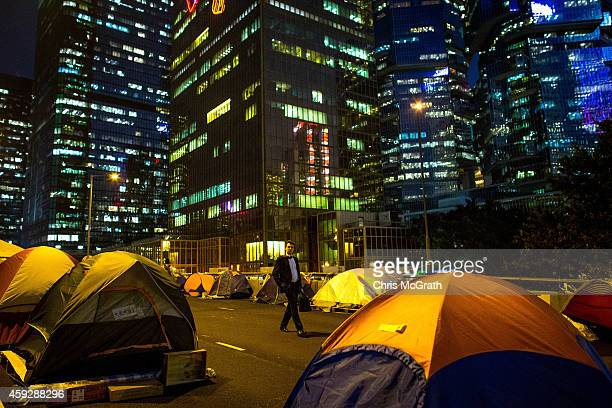 Business man walks through rows of tents setup by pro-democracy activists on the road outside Hong Kong's Government complex on November 20, 2014 in...