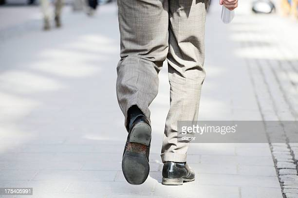 Business man wallking away on tiled street