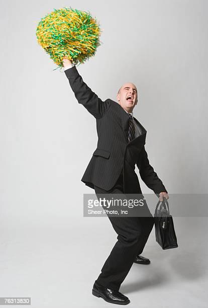Business man waving pompom, studio shot