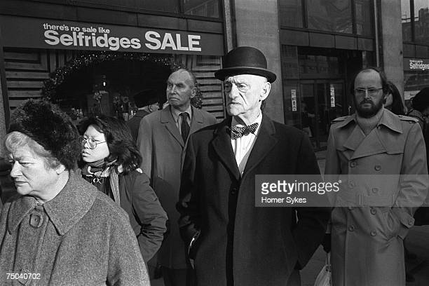 A business man wearing a bowler hat and bow tie queuing outside Selfridges department store Oxford Street on the first day of the New Years sales 1976