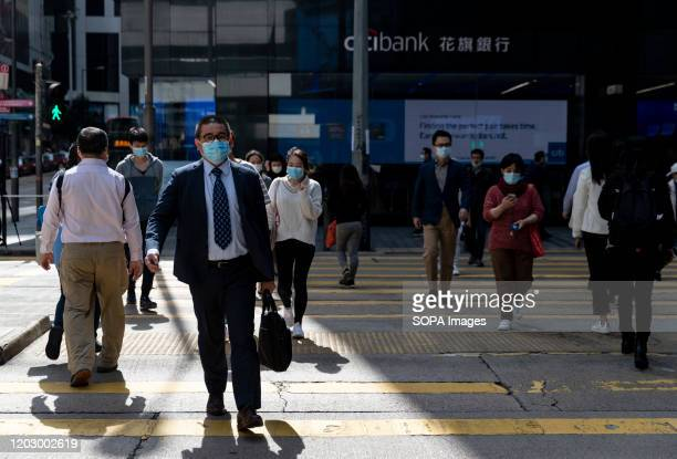 A business man wearing a face mask crosses the road in central a heart of business and financial district Stock markets are falling around the world...