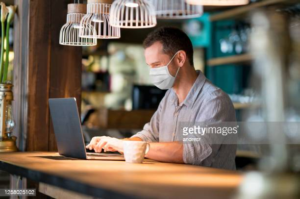 business man wearing a facemask at a cafe - biosecurity stock pictures, royalty-free photos & images