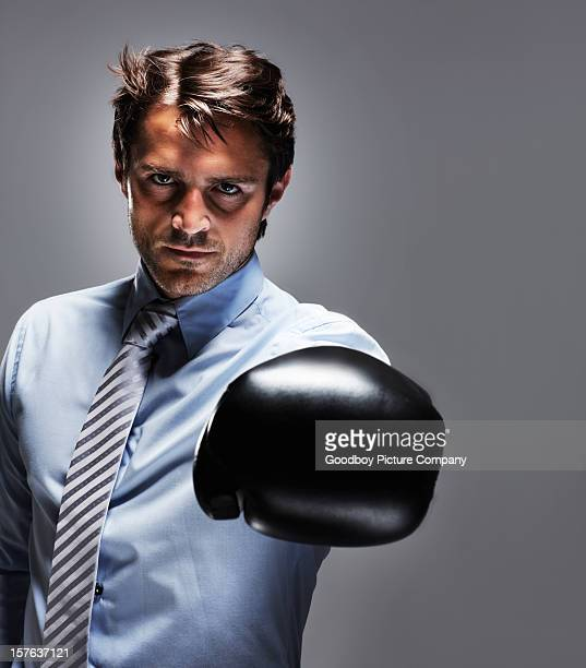 Business man wearing boxing gloves against colored background