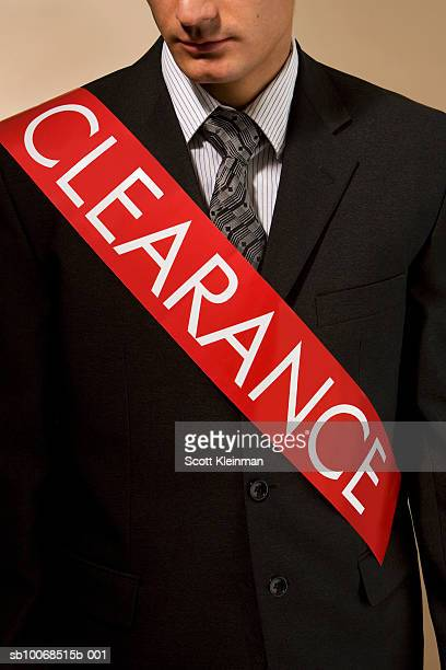 business man wearing sash reading 'clearance', mid section - sash stock pictures, royalty-free photos & images