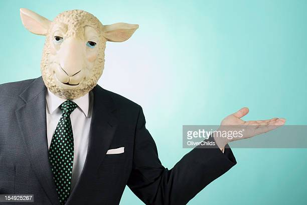 Business man wearing sheep mask presenting.