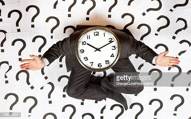Business man with a clock head surrounded by question marks