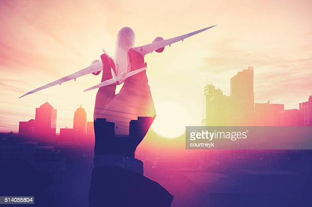 Business man with airplane with cityscape montage.