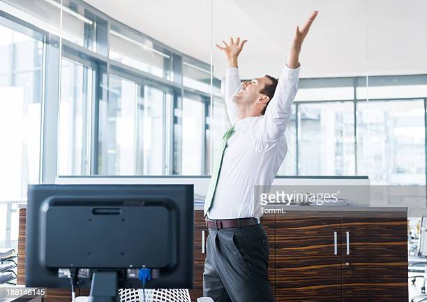 Business man with arms out in modern office