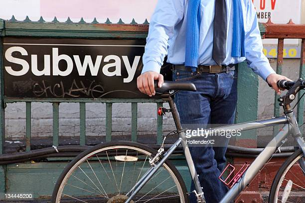business man with bike against subway sign