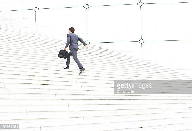 Business man with briefcase running up steps