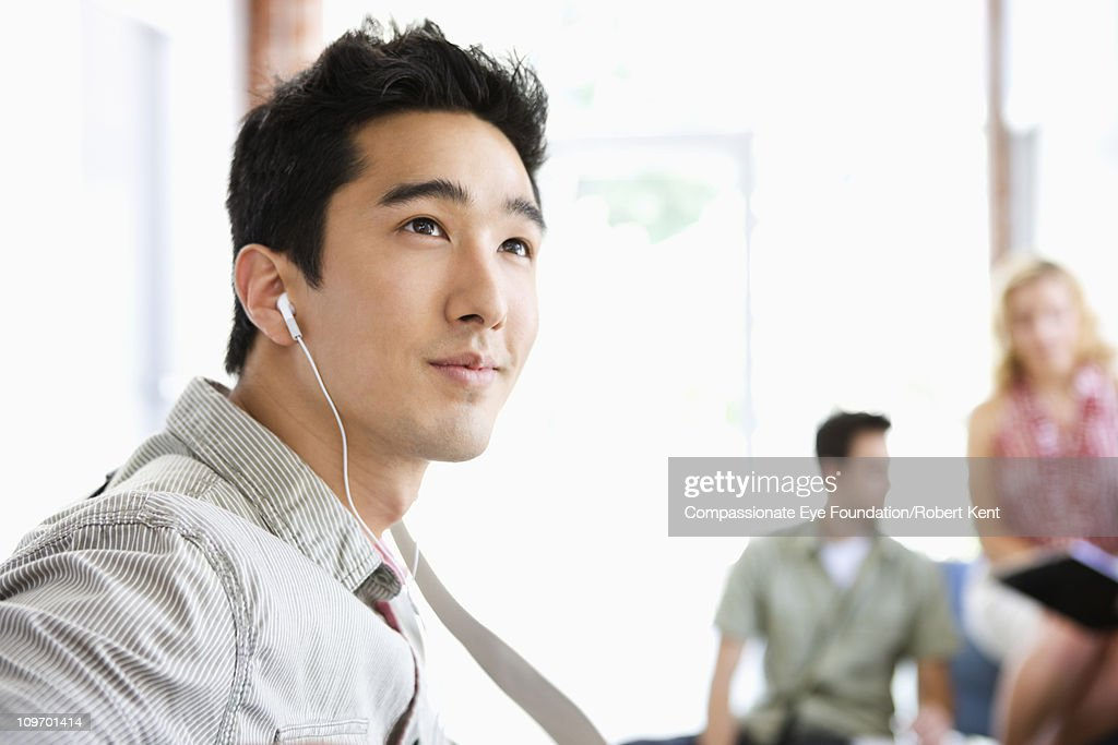 business man with ear buds looking into distance : Stock Photo