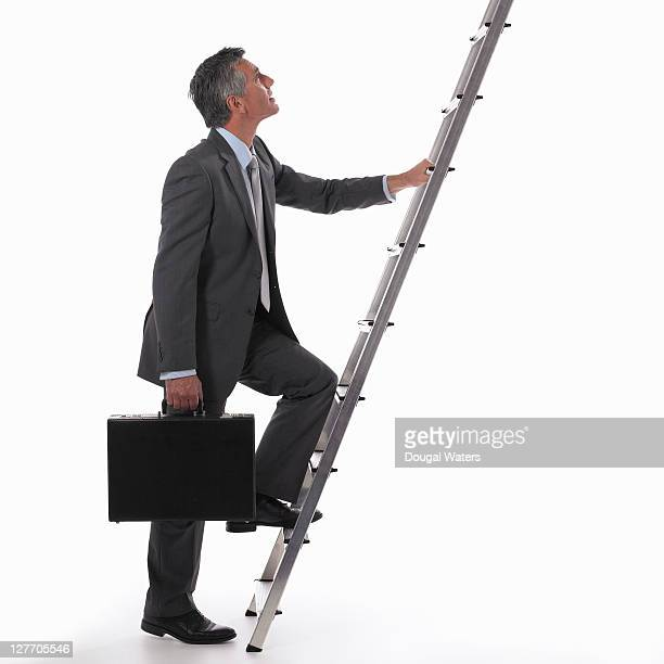 Business man with foot on ladder,
