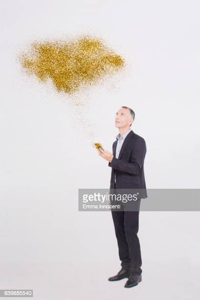 Business man with gold cloud coming from phone