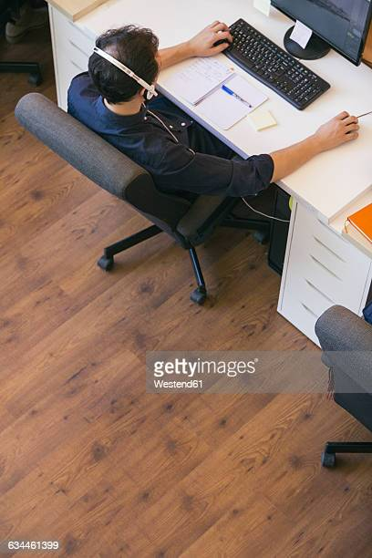 Business man with headphones sitting using a computer in an office