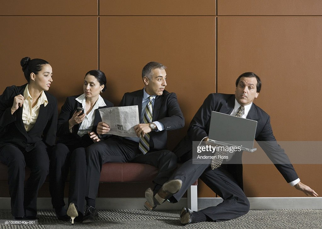 Business man with laptop getting pushed off from bench by businesspeople : Stockfoto