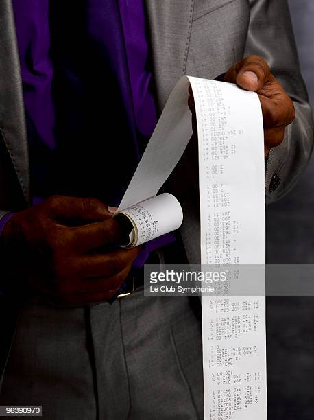 business man with long paper receipt - addierrolle stock-fotos und bilder