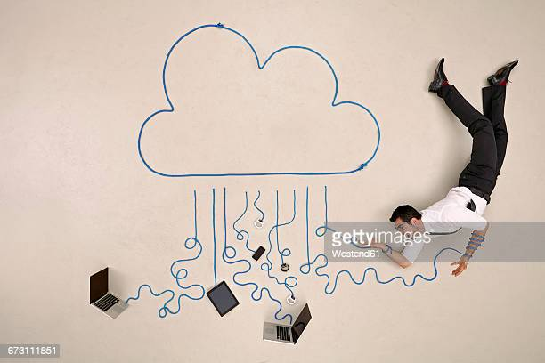 Business man with mobile devices caught in a cloud