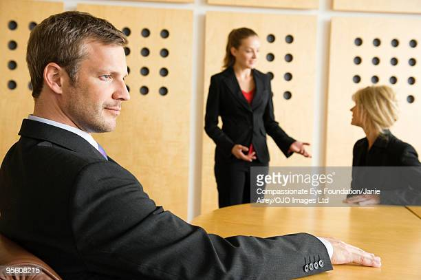 business man with two business women talking