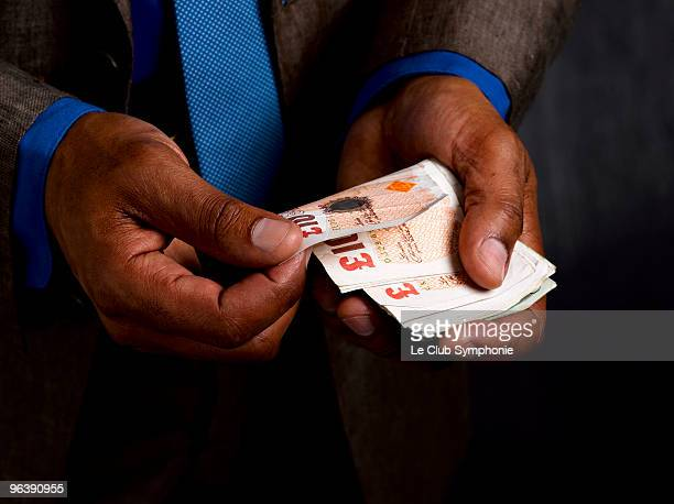 business man with wad of sterling notes - giving stock photos and pictures