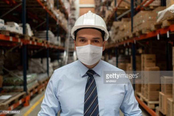 business man working at a distribution warehouse wearing a facemask to avoid covid-19 - biosecurity stock pictures, royalty-free photos & images