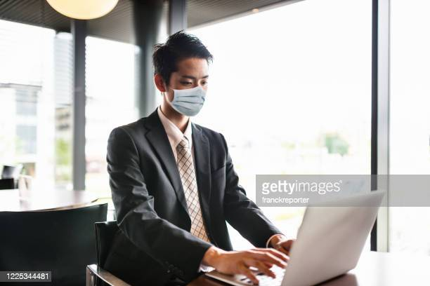 business man working with face mask during the covid19 - businesswear stock pictures, royalty-free photos & images