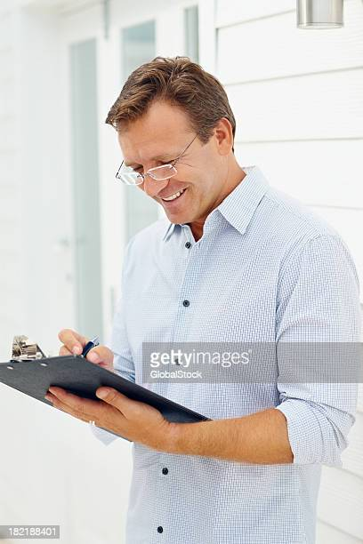 Business man writing on a clipboard