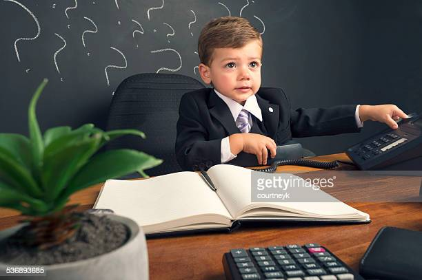 Business manager concept. Young child in a suit working