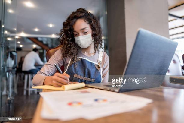 business manager doing the books at a restaurant wearing a facemask - business owner stock pictures, royalty-free photos & images