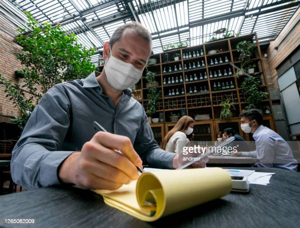 business manager doing the books at a restaurant wearing a facemask - biosecurity stock pictures, royalty-free photos & images