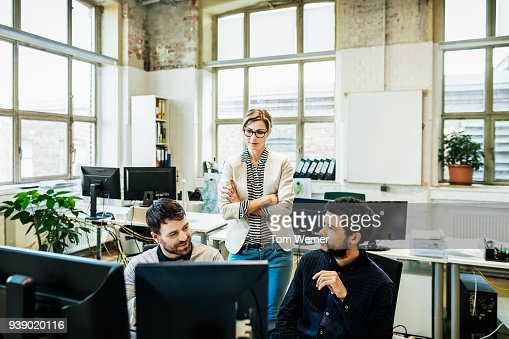 Business Manager Talking To Her Colleagues Working On Computers