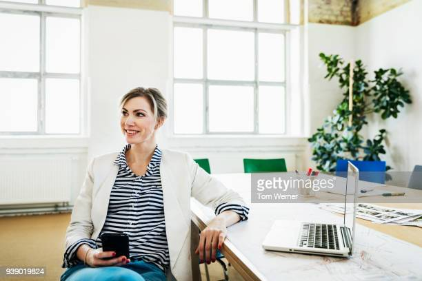 business manager using smartphone after meeting - white blazer stock pictures, royalty-free photos & images