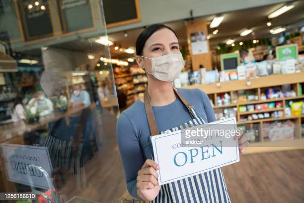 business manager wearing a facemask and holding an open sign at a grocery store - biosecurity stock pictures, royalty-free photos & images