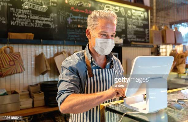 business manager working at a cafe and placing an order at the till and wearing a facemask - reopening stock pictures, royalty-free photos & images