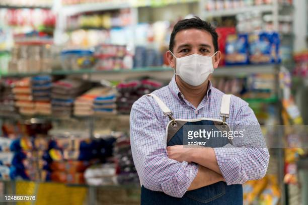 business manager working at a convenience store wearing a facemask - convenience store stock pictures, royalty-free photos & images