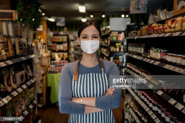 geschäftsführer in einem supermarkt mit einer gesichtsmaske - weibliche angestellte stock-fotos und bilder