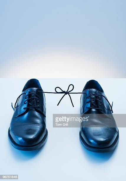 Business man's shoes tied together